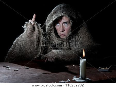 Enclosed nun threateningly raising finger in the dark cell.