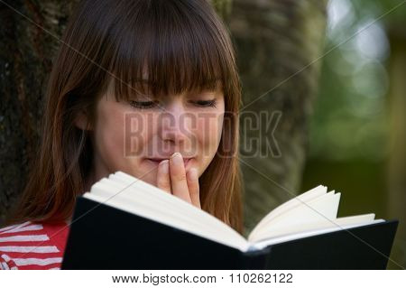 Young Woman Shocked By Reading Novel Outdoors