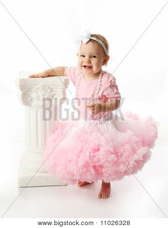Baby Girl Wearing Pettiskirt Tutu And Pearls Standing Next To A White Pedestal Column
