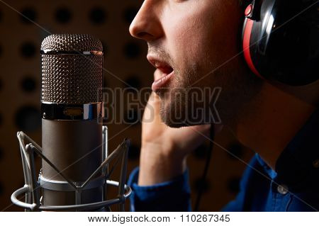 Male Vocalist Singing Into Microphone In Recording Studio