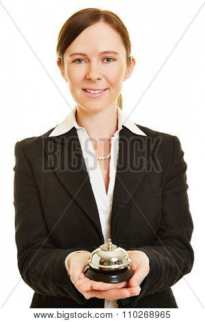 Female bellhop with hotel bell in her hands