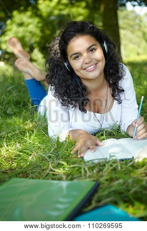 Female Student Revising And Listening To Music In Park