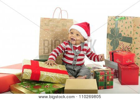 An adorable baby boy delightedly sitting in his Santa hat among many wrapped Christmas gifts.  On a white background.