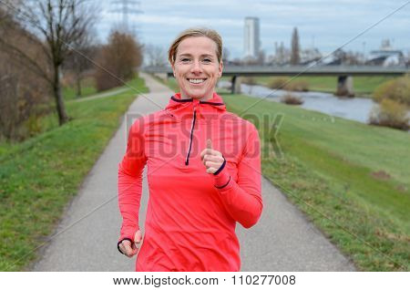 Athletic Adult Woman Jogging Along The Dike