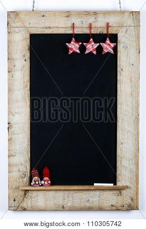 Chalkboard blackboard with red grey fabric stars and small children winter puppet nordic decoration restaurant vintage menu design on painted reclaimed wooden frame on white background with copy space poster