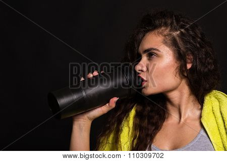 Sports girl drinks water. Beautiful brunette with a towel and shaker on a black background.