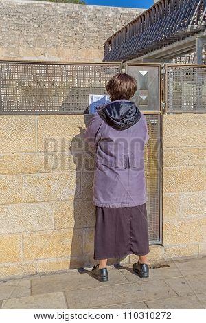 Woman praying outside of the Wailing Wall
