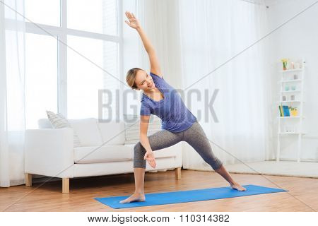 fitness, sport, people and healthy lifestyle concept - woman making yoga bikram triangle pose on mat