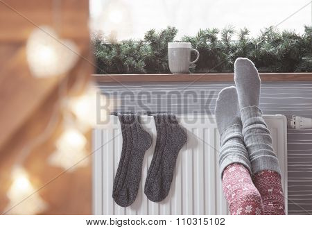 Woman warming up with feet on heater Winter woolen socks drying on a heater, christmas lights, decorations and hot drink
