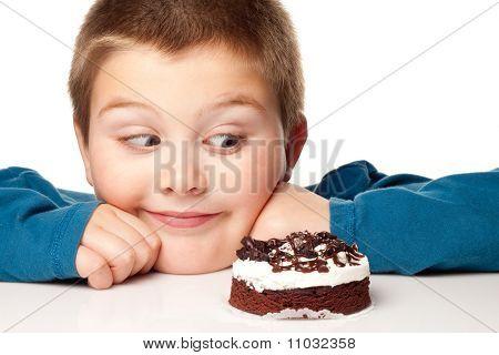 Young Boy Deciding To Eat A Dessert