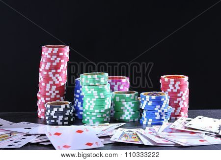 Rolls of poker chips and pile of cards on black background.
