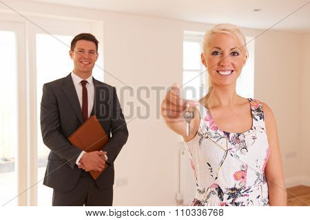 Estate Agent Handing Over Keys Of New Home To Female Buyer