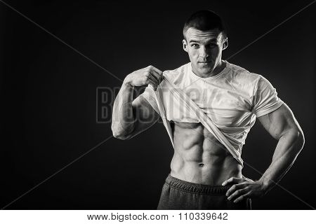 Bodybuilder showing his press. A man shows his abdominal muscles,
