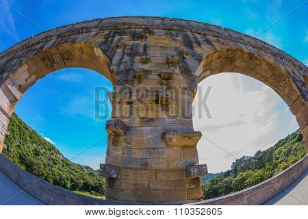 Part of the bridge. One bridge span is photographed lens Fisheye. Three-tiered aqueduct Pont du Gard - the highest in Europe. Provence, spring sunny day