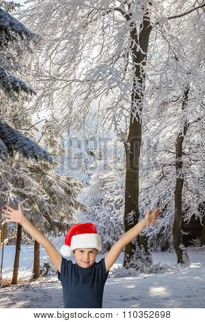 In the snow-covered coniferous wood charming seven-year-old boy in red Santa Claus's cap smiles. The boy threw his hands up in the joyful greeting
