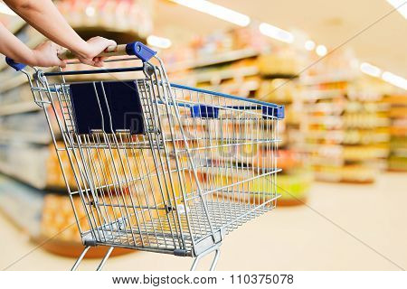 Woman Pushing Shopping Cart In Supermarket