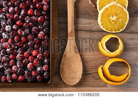 A kitchen sheet of sugared cranberries with wooden spoon and orange peel and slices. Preparation for making Thanksgiving cranberry sauce.