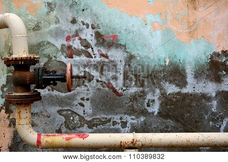Angled metal pipe with valve against colourful peeling wall in Baku, Azerbaijan