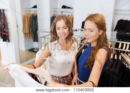 sale, consumerism and people concept - happy young women with shopping bags choosing clothes at clothing shop