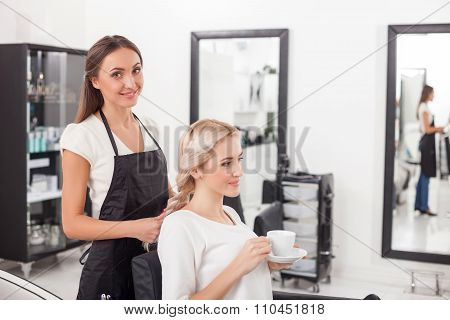Beautiful blond girl is getting hairstyle by hairdresser