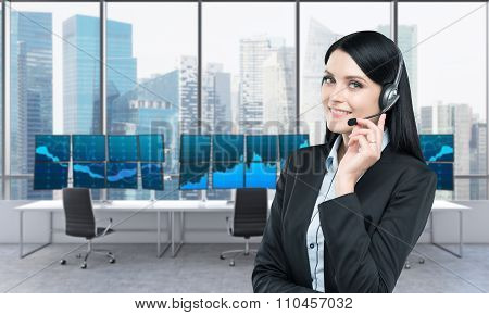 Woman In Headphones In Front Of Screens With Trading Data