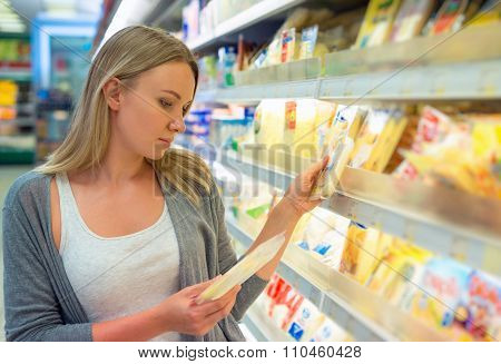 Young woman choosing cheese in grocery store. poster