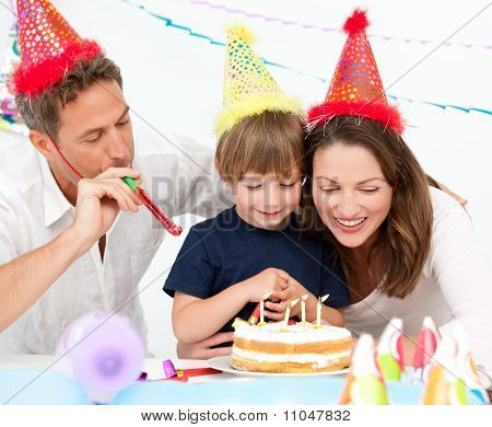 Happy Family Blowing Candles Together For A Birthday