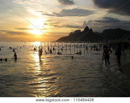 crowded beach at the sunset