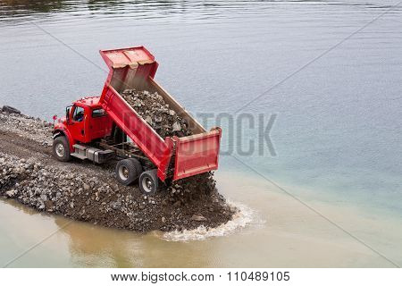 Red Dump Truck Unloading Earth Fill
