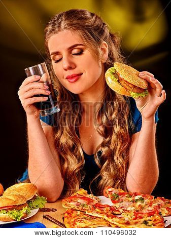 Girl eating  hamburger with pizza and drink cola. Fastfood concept.
