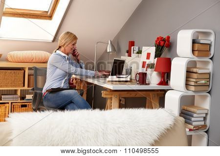 Blonde woman working at home, talking on mobilephone, using laptop computer.