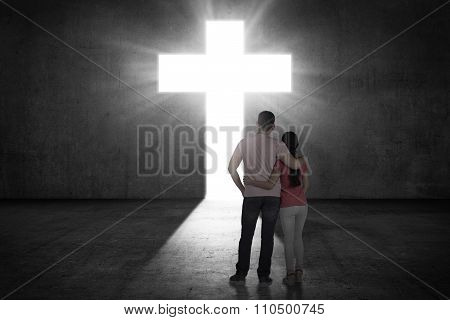 Young Couple Looking The Shining Cross On The Wall