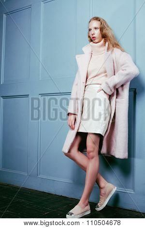 young blonde teenage girl in fur coat, fashion dressed model, studio shot