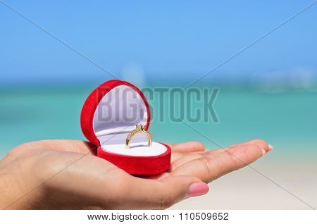 Female Hand Holding Golden Wedding Ring In Red Jewellery Box On The Sandy Beach