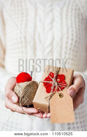 Woman In White Knitted Sweater And Mitts Holding A Present And Coils Of Red Thread And Linen Rope.