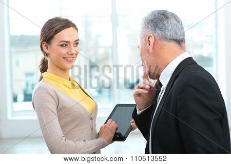 Aged businessman with assistant in office