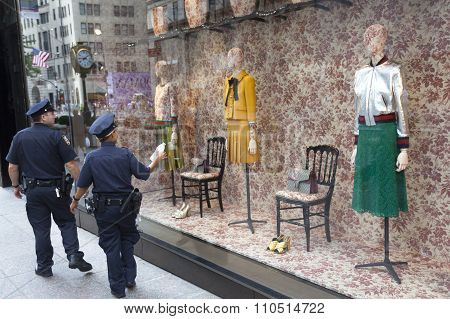 new york city, USA, 15 september 2015: police officers of NYPD pass by window shop of tiffany's on fifth ave