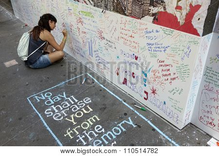 Young Woman Sits On Pavement Near Ground Zero And Writes On Wall For Patriot Day