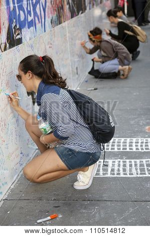 New York City, 11 September 2015: Young Women Sit On Pavement Near Ground Zero And Write On Wall For