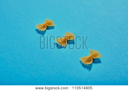 Three Farfale Pasta Pieces On Blue Background