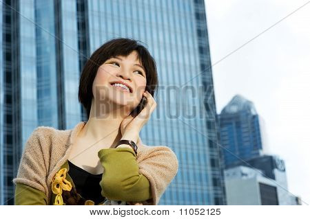 Beautiful Chinese woman talks on the phone. Modern building behind her
