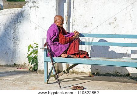 BAGO, MYANMAR - November 24, 2015: Old monk enjoying the sun in Bago Myanmar Buddhism in Myanmar is predominantly of the Theravada tradition, practised by 89% of the country's population