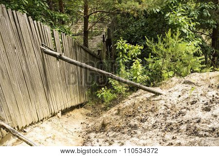 Wooden Fence, Backed By Log And A Pile Of Sand