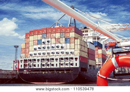 The Rear Part Of A Tall, Laden Container Ship In The Harbor