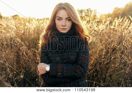 Outdoors noon portrait of serious young beautiful redhead woman in scarf and jacket on faded meadow