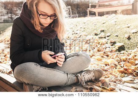 Caucasian Blond Teenage Girl In Jeans With Mobile Phone