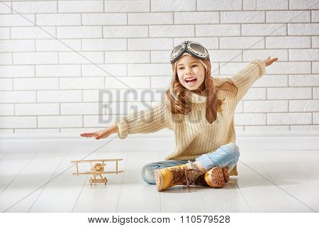 happy child girl playing with toy airplane. the dream of becoming a pilot