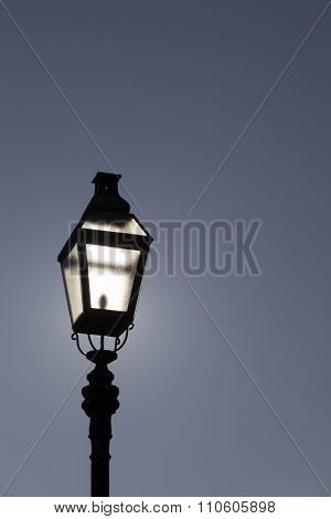 Old street lamp on a background of dramatic dark blue skyBacklight. Highlights sun lustre, shine. Space for text poster