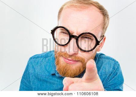 Portrait of suspicious young bearded man in funny round glasses pointing on you isolated over white background