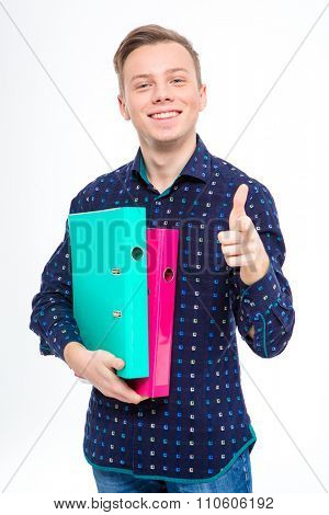 Confident positive young manin checkered shirt holding colorful folders and pointing on you over white background